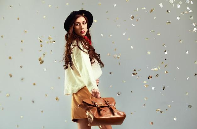 Hermosa joven con una blusa blanca y una falda y un sombrero sobre un fondo gris. en manos de un hermoso bolso de mano. el concepto de moda.