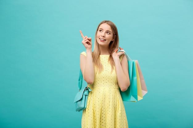 Hermosa joven con bolso de compras en vestido amarillo apunta a algo con su dedo.