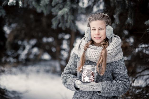 Hermosa joven en bosque de invierno con decoración