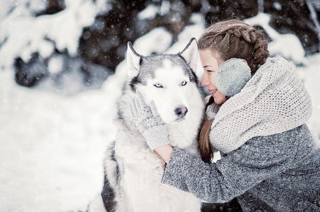 Hermosa joven en bosque de invierno con husky siberiano. símbolo de año nuevo 2018