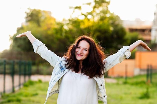 Hermosa joven brazos extendidos y sonrisas en la naturaleza