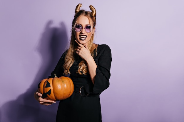 Hermosa joven bruja posando en la pared púrpura. dichosa chica vampiro con calabaza de halloween.