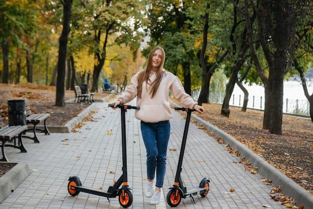 Hermosa joven cabalgando en el parque en scooters eléctricos en un cálido día de otoño.