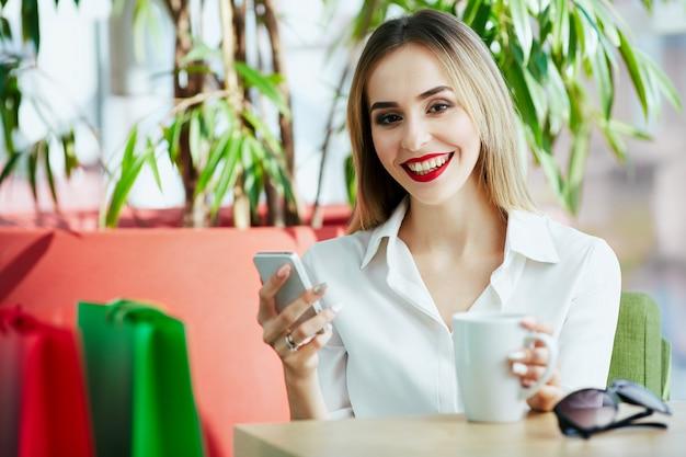 Hermosa joven con cabello castaño claro y labios rojos con blusa blanca y sentada con coloridas bolsas de la compra y una taza de café, sosteniendo el teléfono móvil.