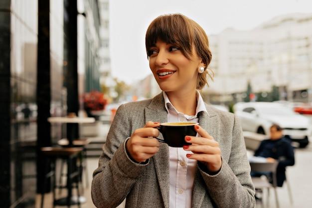 Hermosa joven con cabello castaño está sosteniendo café, estudiante en la cafetería, trabajando en la computadora portátil, disfrutando del trabajo.
