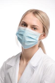 Hermosa joven con cabello rubio en una máscara médica sobre fondo blanco