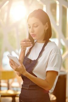 Hermosa joven camarera en delantal de mezclilla de pie en la cafetería y repitiendo el pedido al cliente en el teléfono