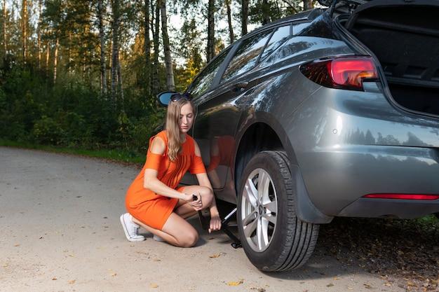 Hermosa joven cambiando rueda dañada y arreglarlo