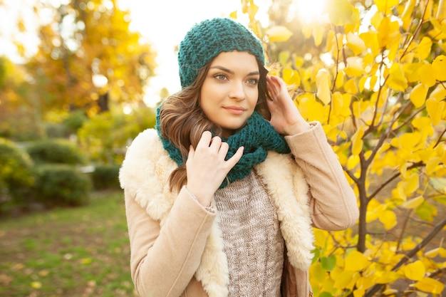 Una hermosa joven camina por el parque de otoño en el fondo de hojas de colores brillantes