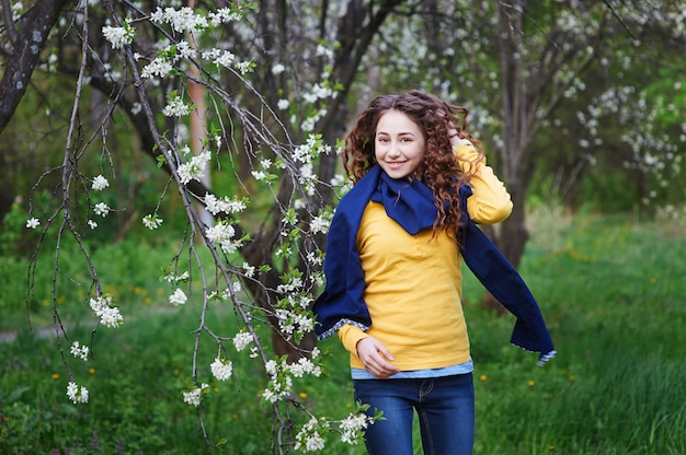 Hermosa joven caminando en un jardín floreciente