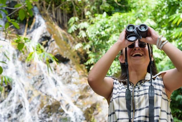 Hermosa joven caminatas está utilizando binoculares para buscar aves en el bosque tropical cerca de las cascadas en tailandia