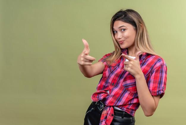 Una hermosa joven con una camisa a cuadros apuntando con el dedo índice sobre una pared verde