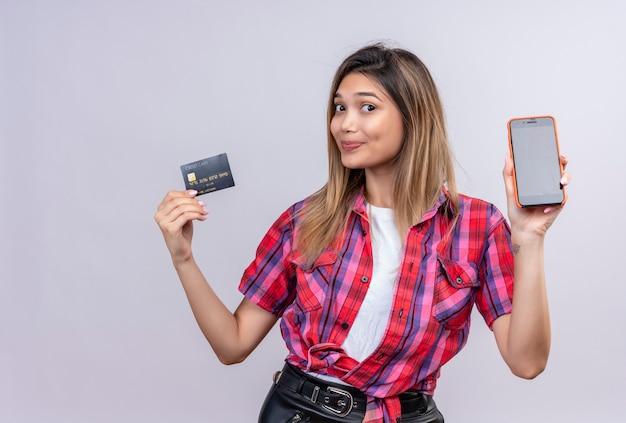 Una hermosa joven con una camisa a cuadros que muestra el espacio en blanco del teléfono móvil y la tarjeta de crédito