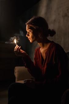 Hermosa joven en camisa roja ilumina su cara bonita con un partido sentado en una habitación oscura y sosteniendo una caja de cerillas en la mano