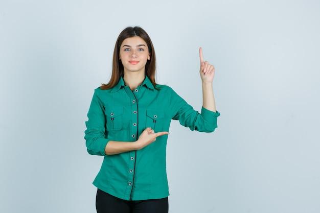 Hermosa joven en camisa verde apuntando hacia arriba y hacia la derecha y mirando confiada, vista frontal.