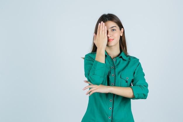 Hermosa joven en camisa verde sosteniendo la mano en el ojo y mirando optimista, vista frontal.