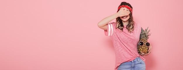 Hermosa joven en camiseta rosa, cubre su rostro, sostiene piña