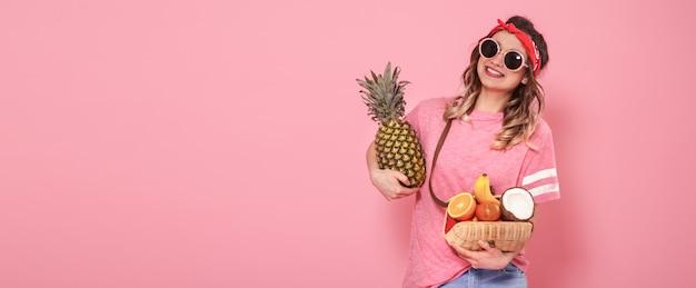 Hermosa joven en camiseta rosa y gafas, sostiene una bolsa de paja llena de frutas sobre fondo rosa