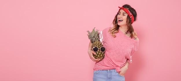 Hermosa joven en camiseta rosa, sonriendo con piña en pared rosa