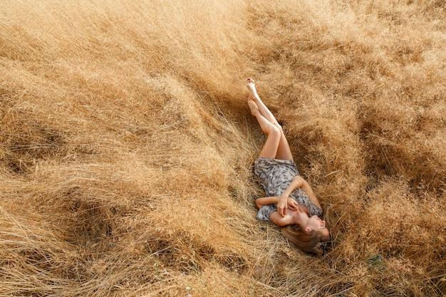 Hermosa joven está en campo de trigo en un día soleado.