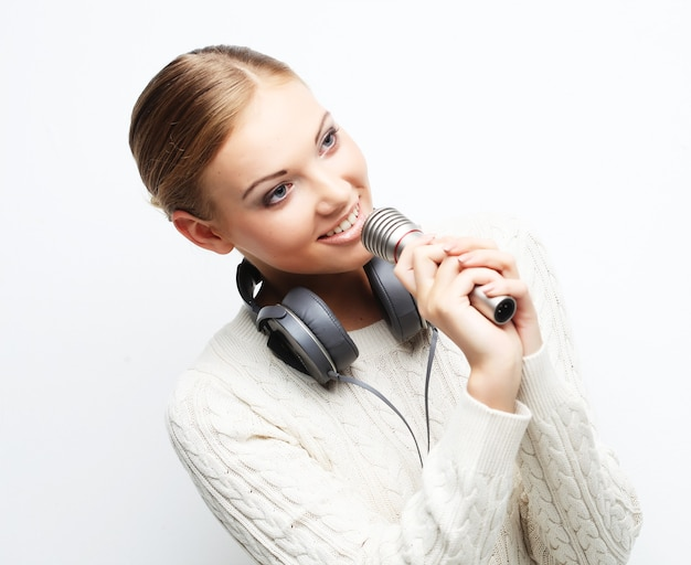 Hermosa joven cantando en micrófono con auriculares en espacio en blanco