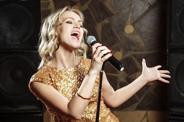 Hermosa joven cantando con el micrófono.