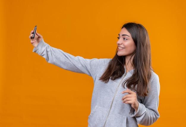 Hermosa joven con capucha gris haciendo selfie con una sonrisa en la cara de pie sobre fondo naranja