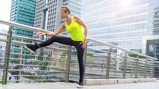 Hermosa joven caucásica en fitness desgaste haciendo ejercicios en la ciudad al aire libre.