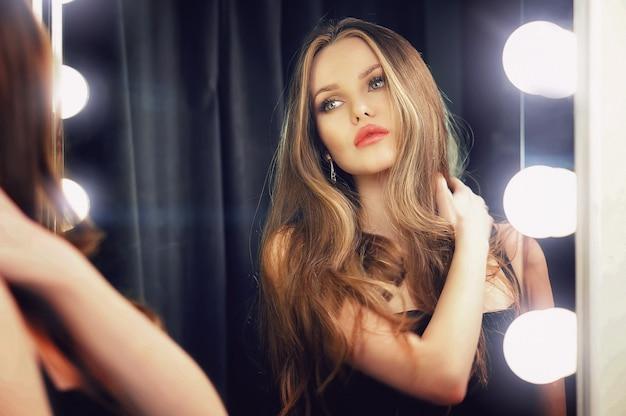 Hermosa joven caucásica mirando en el espejo de maquillaje a sí misma y disfrutando de su tiempo