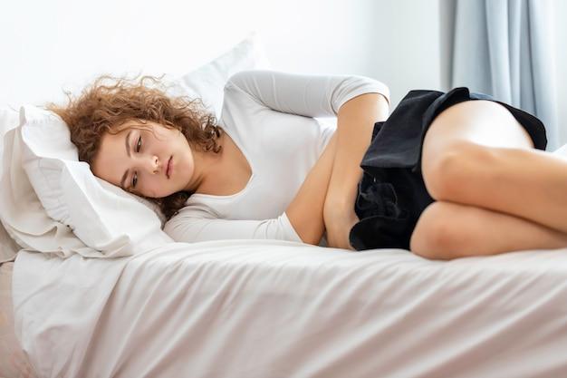 Hermosa joven caucásica paciente con dolor menstrual en la habitación de la cama.