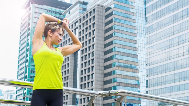 Hermosa joven caucásica en ropa de fitness haciendo ejercicios en la ciudad al aire libre.