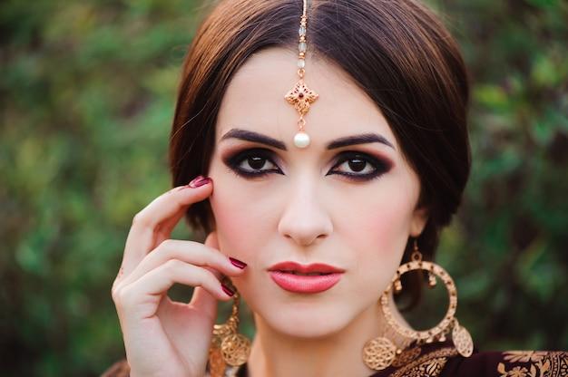 Hermosa joven caucásica en sari de ropa tradicional india con maquillaje de novia y joyas y tatuaje de henna en las manos
