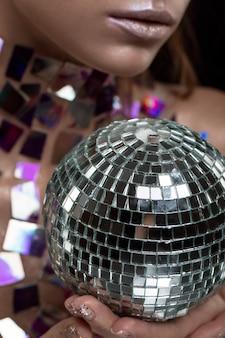 Hermosa joven caucásica sosteniendo bola de discoteca