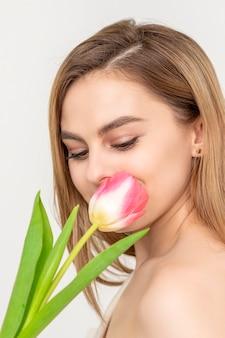 Hermosa joven caucásica con un tulipán en busca de una flor sobre un fondo blanco.