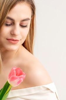 Hermosa joven caucásica con un tulipán sobre fondo blanco.