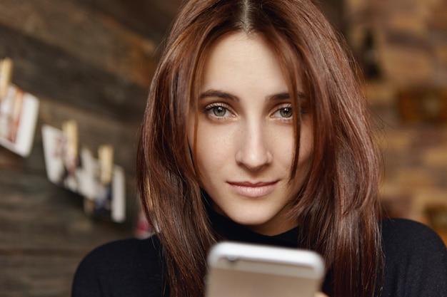 Hermosa joven caucásica wirh cabello oscuro con teléfono celular, mensajes a amigos en línea o navegar por internet sentado en el interior de la cafetería moderna. concepto de personas, tecnología y comunicación.