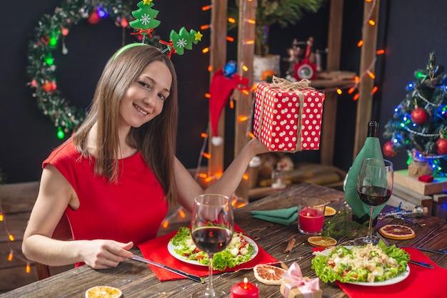 Hermosa joven cenando en la mesa navideña con caja de regalo roja en adornos navideños