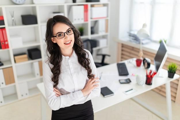 Una hermosa joven se para cerca de la mesa de la oficina, con las manos juntas en el pecho.