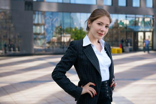 Una hermosa joven en una chaqueta y camisa blanca posa con el telón de fondo de un edificio de oficinas en un día soleado