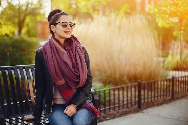 Hermosa joven en una chaqueta de cuero y bufanda sentada en las calles de chicago