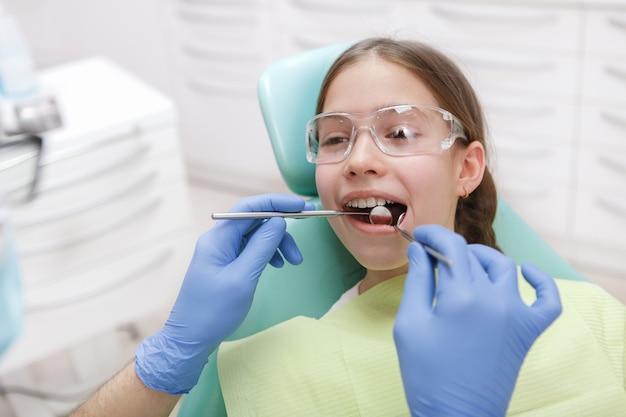 Hermosa joven en el chequeo dental en la clínica