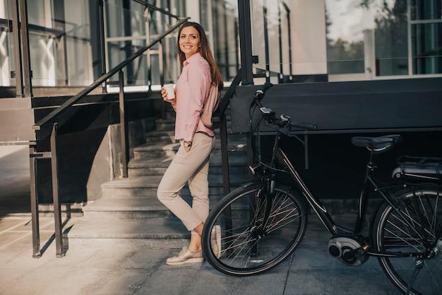 Hermosa joven ciclista bebe café caliente de una taza junto a la bicicleta eléctrica en el entorno urbano