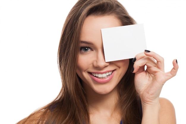 Hermosa joven cierra los ojos con tarjeta