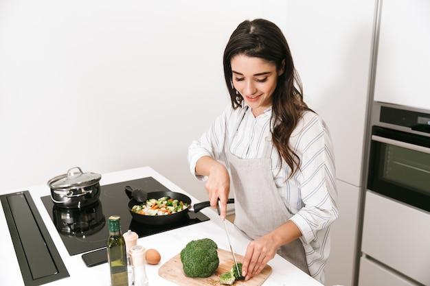 Hermosa joven cocinando una cena saludable en la cocina, usando una sartén