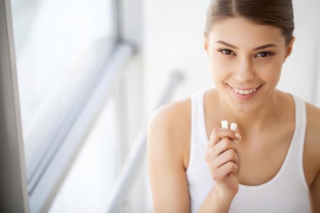 Hermosa joven comiendo chicle, sonriendo