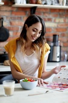 Hermosa joven comiendo una ensalada saludable y leyendo una revista