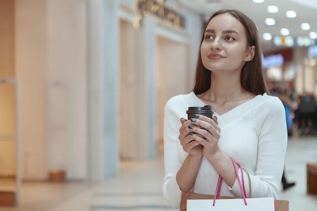 Hermosa joven de compras en el centro comercial local