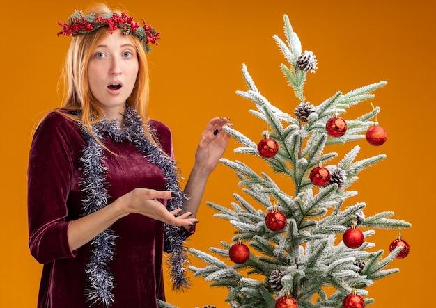 Hermosa joven confundida de pie cerca del árbol de navidad con vestido rojo y corona con guirnalda en el cuello aislado sobre fondo naranja