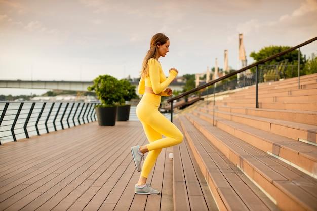 Hermosa joven corriendo en las escaleras a la orilla del río