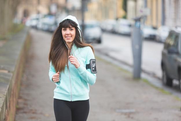 Hermosa joven corriendo solo en la calle de la ciudad